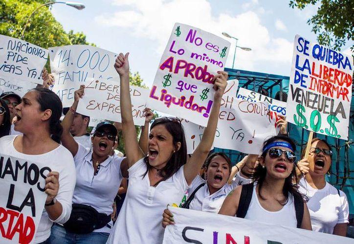 Trabajadores de medios de comunicación impresos y estudiantes de comunicación social de diferentes universidades participan en una protesta en demanda de divisas para la importación de papel periódico, en Caracas, Venezuela. (EFE)