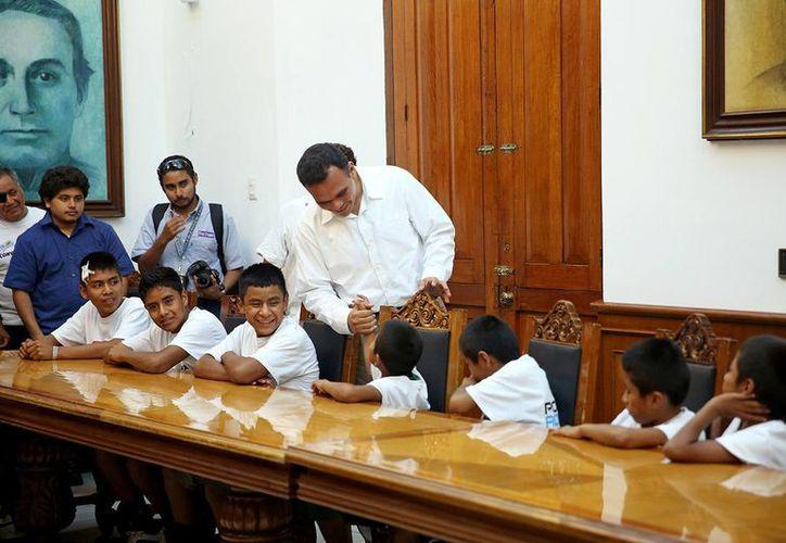 El gobernador de Yucatán, Rolando Zapata Bello, saluda a niños triquis durante la visita que realizaron este viernes a la sede del Poder Ejecutivo del Estado. (SIPSE)