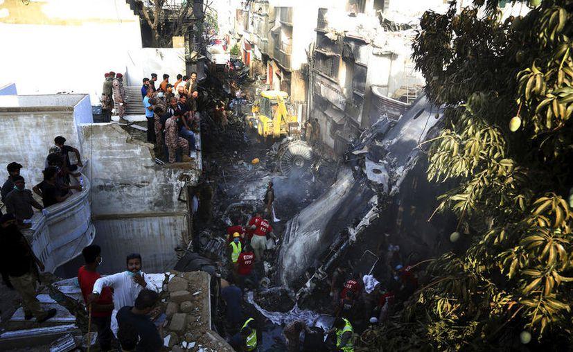Voluntarios buscan sobrevivientes en un accidente de avión en una zona residencial de Karachi, en Pakistán, el 22 de mayo de 2020. (AP Foto/Fareed Khan)