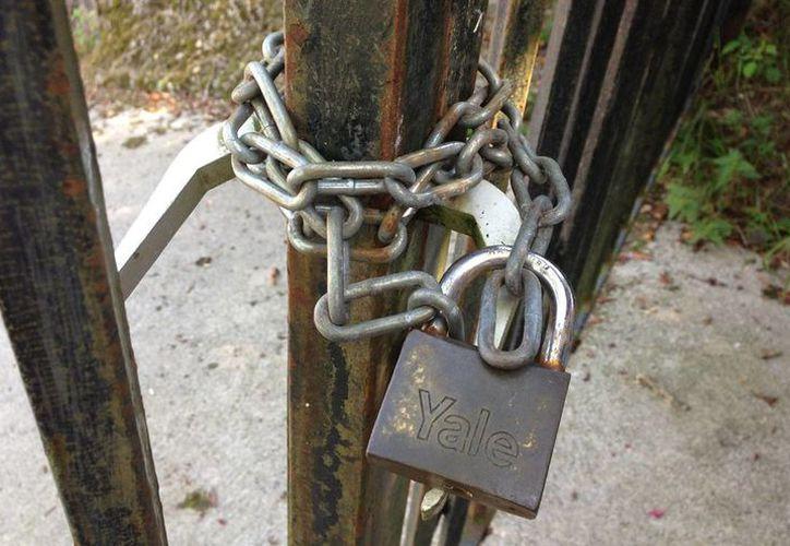 La mujer fue acusada por romper los candados de un predio para instalarse en el lugar. Imagen de una reja cerrada con una cadena. (Archivo/Agencias)