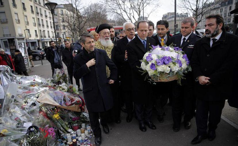 El alcalde de Jerusalén Nir Barkat, al centro, con el rabino Shlomo Amar, segundo a la izquierda, deposita una corona de flores afuera de un mercado judío en París donde el 9 de enero Amedy Coulibaly mató a cuatro personas, el miércoles 21 de enero de 2015.  (Agencias)