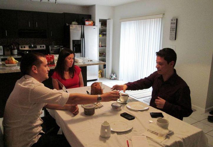 Isabel Rodríguez (izq), otrora conocida como Juan, le pasa el azúcar a su esposo, Felipe Sousa-Rodríguez, en la casa de su hermana en Davie, Florida, el 23 de diciembre del 2014. (Agencias)