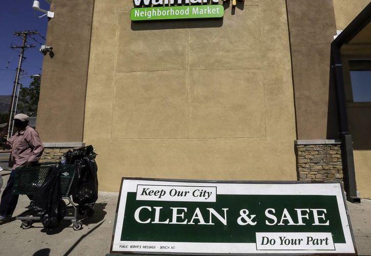 Un trabajador de servicio público pasa frente a una nueva tienda de Walmart abierta en el barrio Altadena de Los Angeles, Californbia. (Agencias)