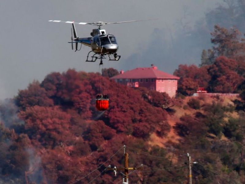 A helicopter battling a fire on Mt. Diablo passes a home covered in fire retardant, Wednesday, July 25, 2018, above Marsh Creek Road east of Clayton, Calif.