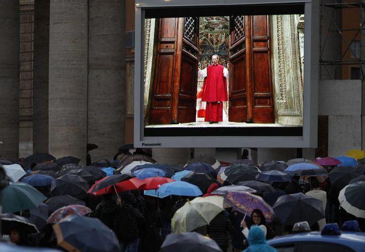 La gente ve en un monitor en donde se ve al monseñor Guido Marini, maestro de ceremonias litúrgicas, como cierra las puertas dobles de la Capilla Sixtina. (Agencias)