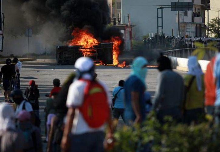 Los empresario yucatecos se manifestaron contra los actos violentos que suceden en el país. En la imagen, un grupo de manifestantes observan un vehículo en llamas durante una marcha de protesta en Guerrero. (Notimex/Archivo)