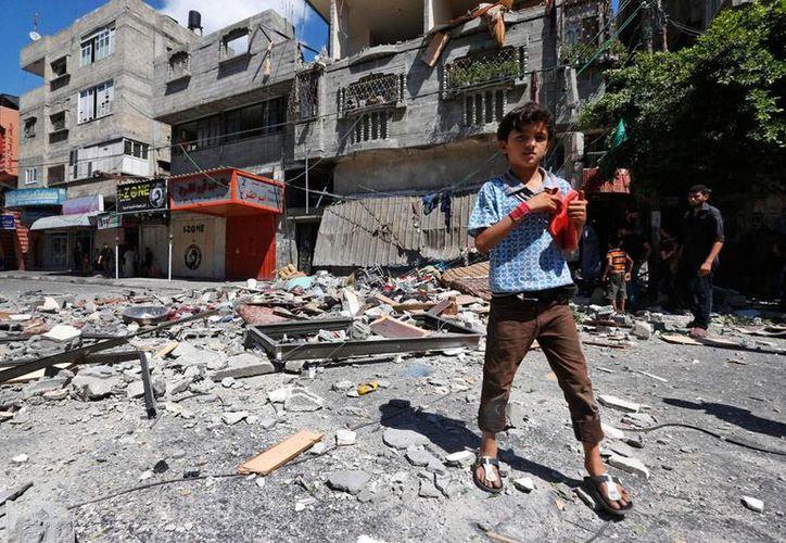 Un niño camina cerca de un edificio derrumbado a causa de una incursión israelí en la Franja de Gaza. Según las autoridades palestinas, en el ataque murieron 20 personas. (AP)