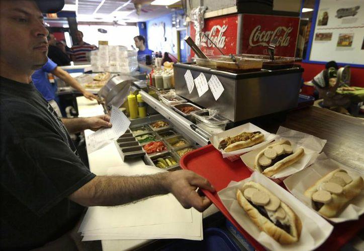 Un empleado de Hot Doug's prepara una orden de hot dogs, el 7 de mayo. El establecimiento anunció que cerraría después de 13 años de servicios. (Foto: Spencer Green/AP)