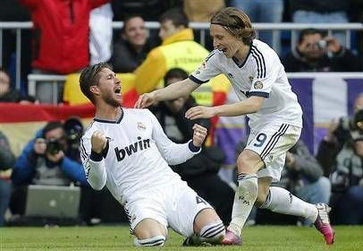 El jugador del Real Madrid, Sergio Ramos (i) festeja con Modric tras anotar contra el Barcelona. (AP Photo/Paul White)