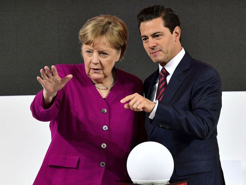 German Chancellor Angela Merkel, left, and Mexican President Enrique Pena Nieto chat as they tour the Hannover Messe fair where Mexico is this year's guest country in Hannover, northern Germany.