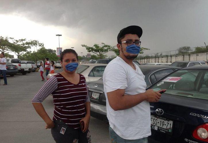 En zona metropolitana de Colima y la conurbada ciudad de Villa de Álvarez registraron hoy una intensa y densa caída de ceniza arrojada por el Volcán de Colima. Imagen de una pareja con tapabocas para protegerse de las cenizas. (Notimex)