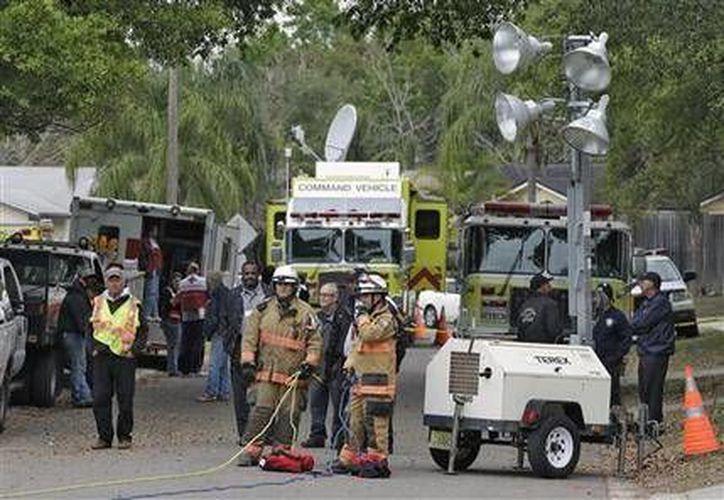 Los bomberos del condado de Hillsborough, Florida, trabajan cerca de donde se abrió un hoyo en la tierra. (Agencias)