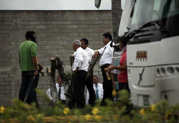 Manifestante enmascarado habla con choferes de autobuses tomados por los manifestantes en una marcha en Acapulco, México. (Agencias)