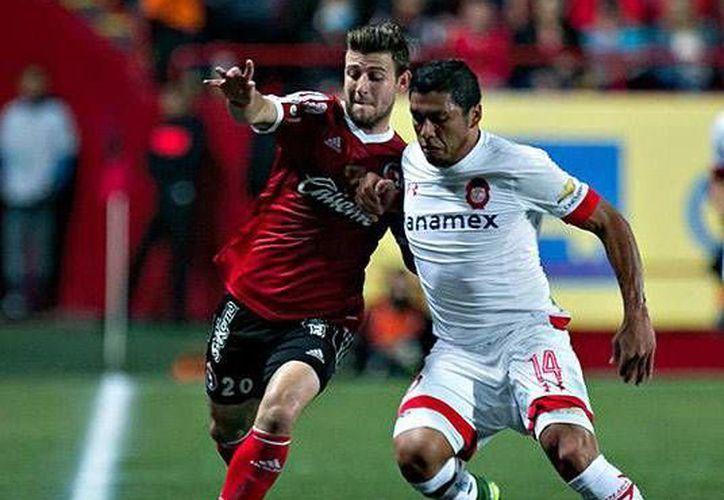 En la foto, Paul Arriola (Xolos) disputa un balón frente a su rival Richard Ortíz. (Foto tomada de Facebook/ Club Tijuana Xoloitzcuintles de Caliente)