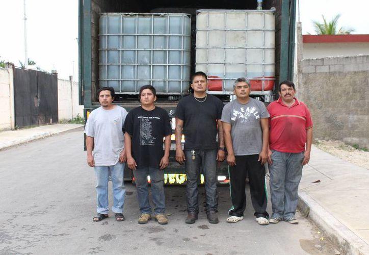 Los hombres que fueron detenidos cuando descargaban en el sur de Mérida miles de litros de combustible robado en Tabasco. (SIPSE)