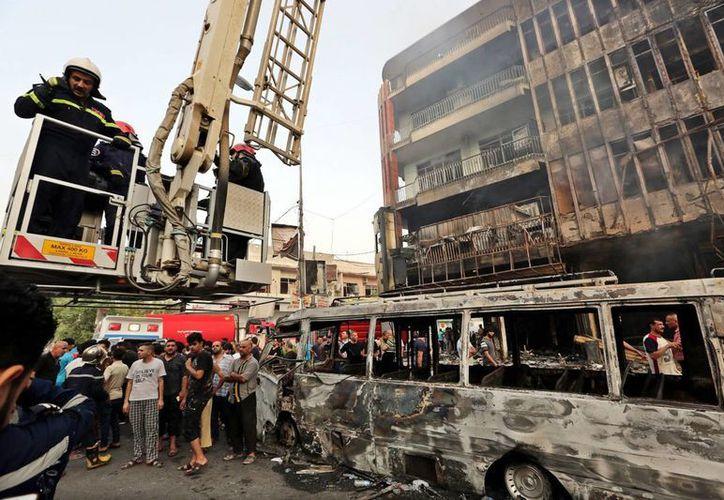 Los bomberos trabajan en el distrito de Karada en el centro de Bagdad, tra la explosión este domingo de un coche bomba. (EFE)