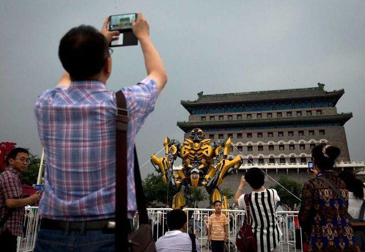 Visitantes toman fotos de una réplica de Bumblebee, a las afuera de Qianmen Gate, en Beijing, como parte de la promoción de la película 'Transformers'. (AP)