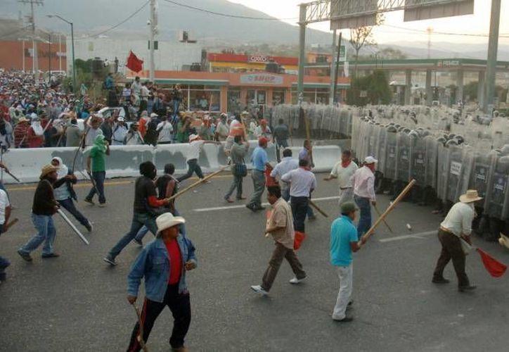 Foto de archivo de un enfrentamiento entre maestros disidentes de la CNTE y autoridades en septiembre del año pasado en Michoacán. (Agencias)