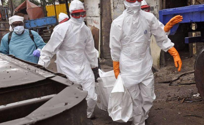 Autoridades de Salud trasladan en Monrovia, Liberia, el cadáver de un hombre que al parecer falleció debido a que se infectó con el virus del ébola. (Foto: AP)