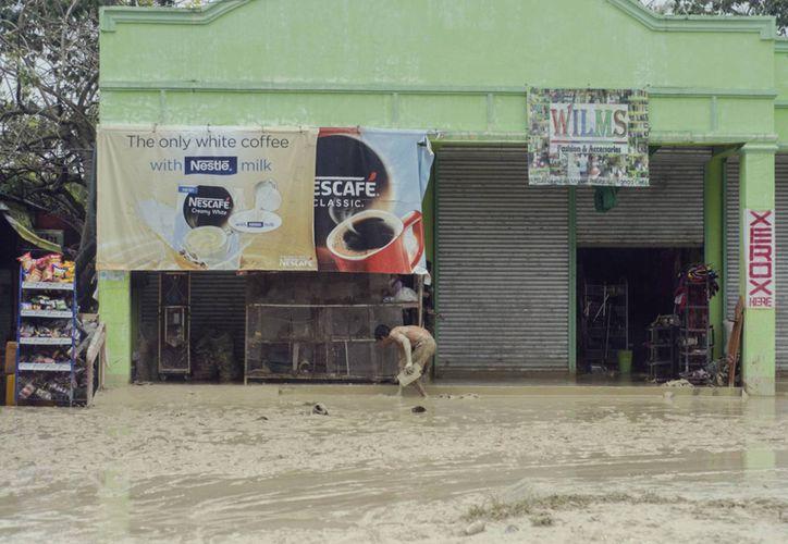 Un residente despeja el barro fuera de su establecimiento comercial en el municipio de Alcántara, provincia de Cebú en Filipinas. (Agencias)