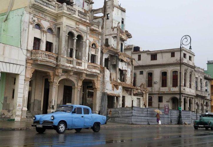 Un auto viejo pasa junto a edificios en muy mal estado frente al Malecón en La Habana Vieja. (Agencias)