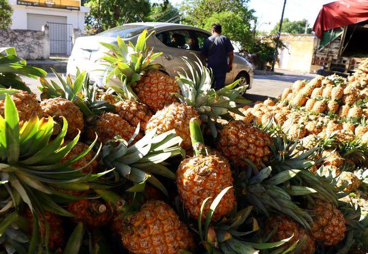 Los vendedores de piña en ocasiones tienen que rematar su producto. (Foto: Jorge Acosta/ Milenio Novedades)