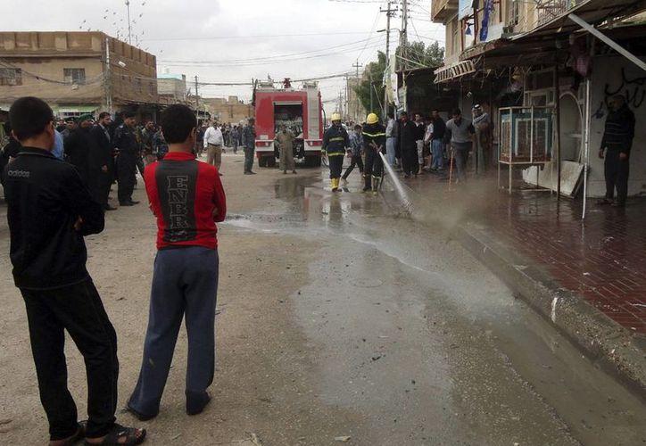 Ciudadanos observan trabajar a bomberos en la ciudad de Najaf, en el sitio donde una bomba detonó y causó heridas a dos personas. (EFE)
