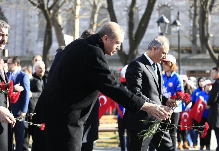 El presidente de Turquía, Recep Tayyip Erdogan, deja un clavel en el sitio de la explosión en el histórico distrito de Sultanahmet en Estambul. La policía detuvo a 18 académicos que estaban entre los más de mil firmantes de una declaración de rechazo a las operaciones militares contra los rebeldes kurdos en Turquía. (Foto AP/Lefteris Pitarakis, Pool)