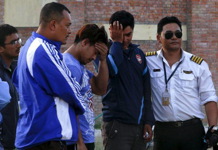 Los familiares de las víctimas de un helicóptero accidentado lamentan la tragedia, mientras los cuerpos son trasladados al hospital universitario de Katmandú, Nepal. (EFE)