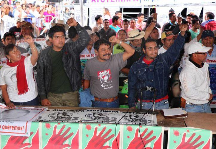 Familiares de los normalistas de Ayotzinapa al final de una conferencia en el Zócalo capitalino luego de la reunión que tuvieron con el presidente Enrique Peña Nieto. (Agencias)