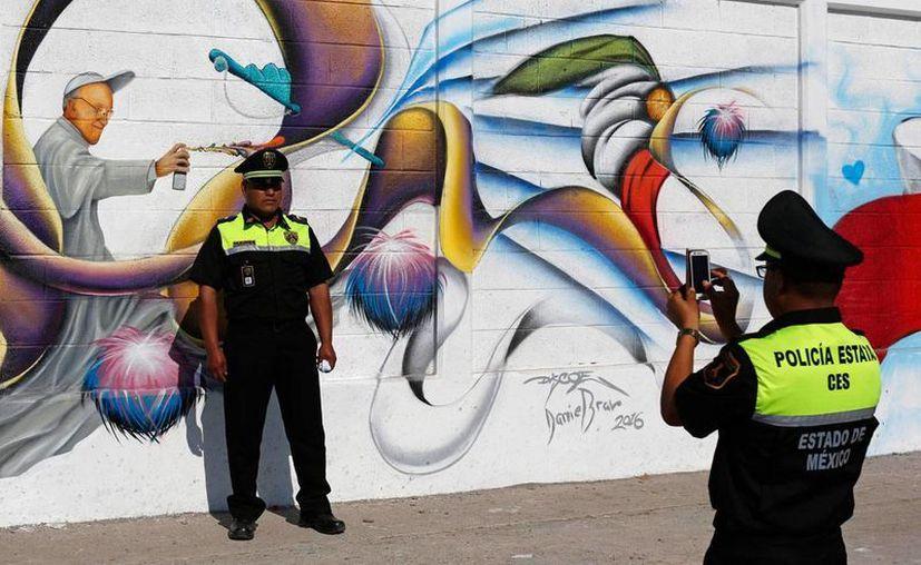 En imagen del viernes 5 de febrero de 2016, un policía toma una foto a un compañero ante un mural con la imagen del papa Francisco como artista del graffiti, en Ecatepec, Estado de México, donde el Papa Francisco oficiará una misa el domingo 14 de febrero. (AP Foto/Dario Lopez-Mills)