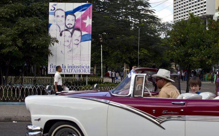 """Un turista pasa frente a un cartel que muestra los retratos de """"Los Cinco"""" en La Habana, Cuba. Son agentes de inteligencia cubanos, integrantes de la llamada """"Red Avispa"""" que operaba en la Florida en la década de 1990.  (Agencias)"""