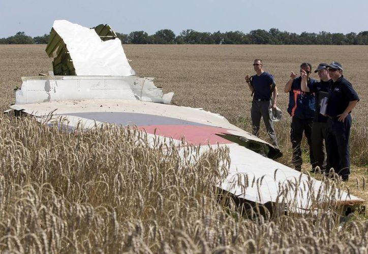 Investigadores examinan un pedazo del avión del vuelo 17 de Malaysia Airlines cerca de la aldea de Hrabove, región de Donetsk, en el este de Ucrania. (Agencias)