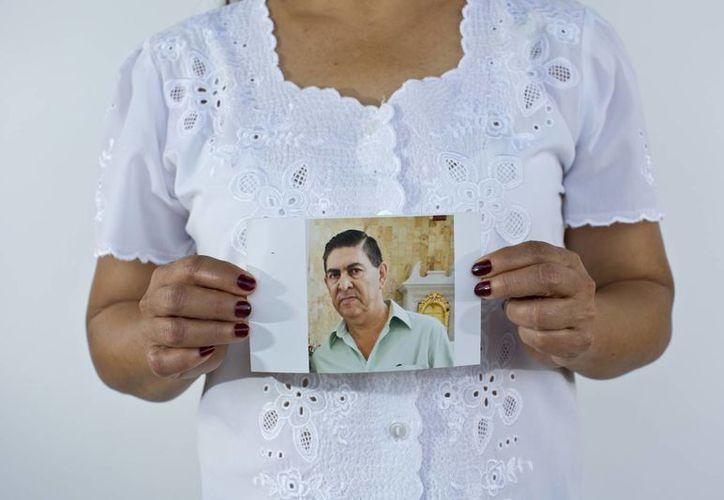 Yolanda Álvarez Antúnez sostiene una imagen de su esposo, Luis Alberto Castillo, quien fue secuestrado en 2013. (Agencias)