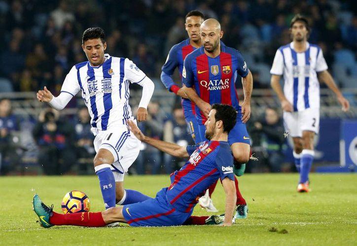 El delantero mexicano de la Real Sociedad, Carlos Vela (i), intenta llevarse el balón ante la entrada del centrocampista del F. C. Barcelona, Sergio Busquets, durante el encuentro correspondiente a la jornada 13 de primera división, en el estadio Anoeta de San Sebastián. (EFE)