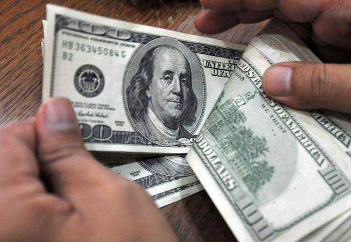 El tipo de cambio para solventar obligaciones denominadas en moneda extranjera pagaderas en el país es de 16.5959 pesos. (Archivo/AP)