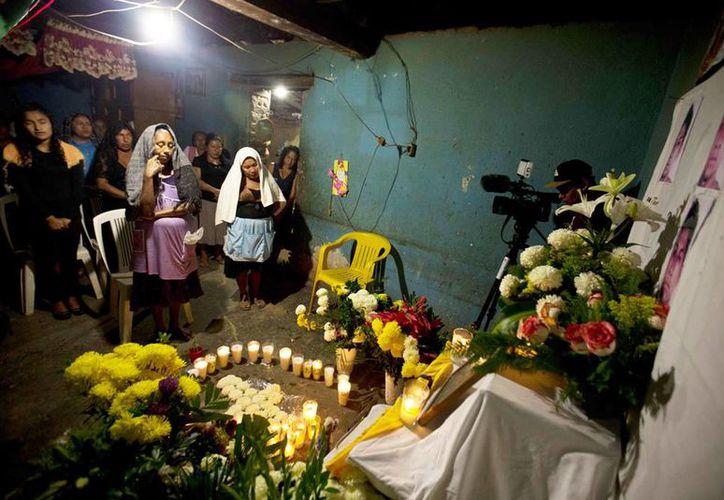 Mujeres de la localidad, de El Pericón, rezan frente a un altar a la memoria de Alexander Mora, uno de los 43 estudiantes desaparecidos, cuyo cuerpo fue identificado positivamente entre los restos calcinados. (Agencias)