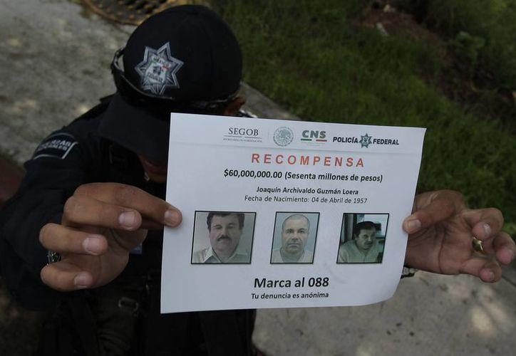 """Un policía muestra un aviso de recompensa por información del paradero del narcotraficante Joaquín """"El Chapo"""" Guzmán. (EFE/Archivo)"""