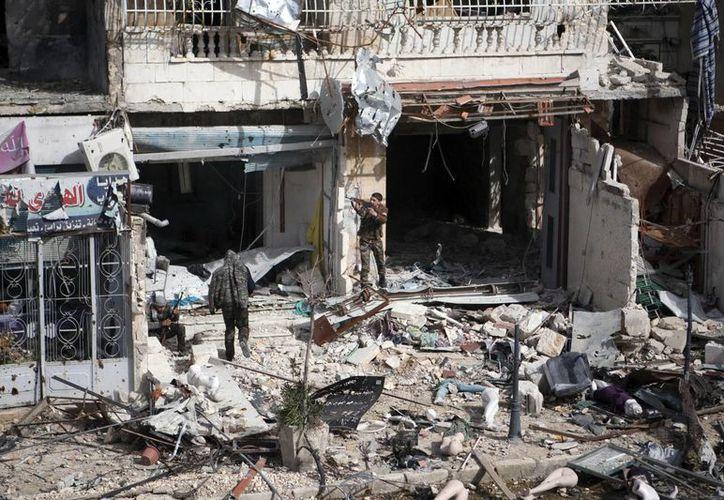 Varios combatientes del Ejército Libre Siro (ELS) rastrean un edificio en Alepo, Siria. (Archivo/EFE)