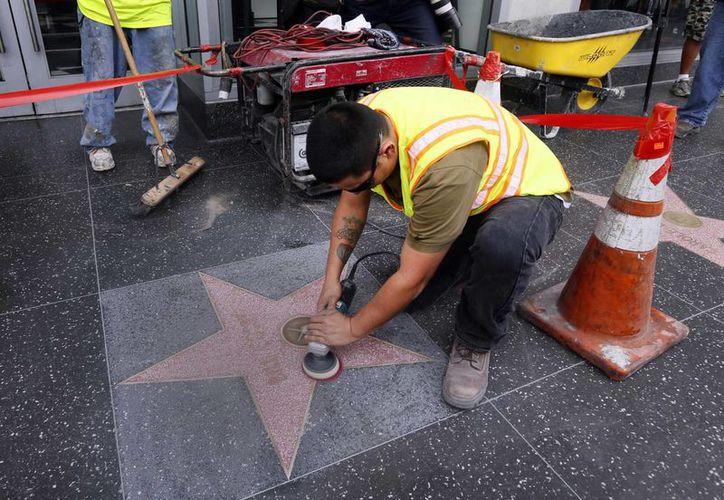 Un grupo de trabajadores limpia la estrella de Bill Cosby en el Paseo de la Fama de Hollywood después de que fuera vandalizada. (Agencias)