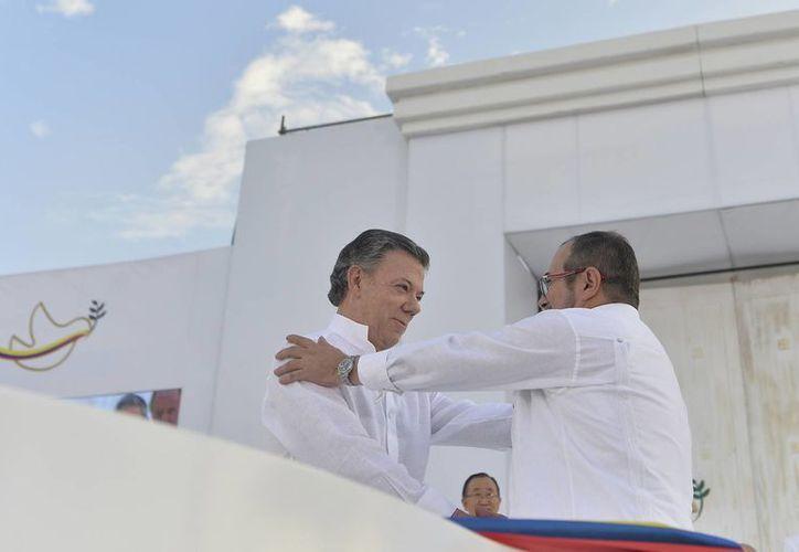 El presidente colombiano Juan Manuel Santos y el jefe de las FARC de saludan, previo a la firma del Acuerdo de Paz, que puso fin a 52 años de conflicto interno con ese grupo rebelde, el lunes 26 de septiembre de 2016. Ahora, Santos urge al Ejército de Liberación Nacional a concretar un acuerdo similar. (Notimex)