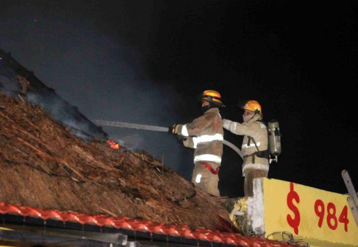 Bomberos llegó al llamado de emergencia para sofocar la palapa que ardía en llamas. (Foto: SIPSE)