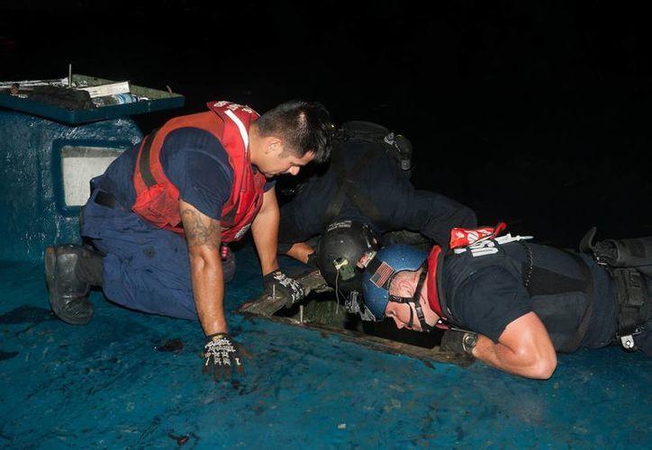 En fotografía, la Guardia Costera estadounidense revisa una nave semisumergida, proveniente de Colombia, que contenía un alijo valorado en más de 200 millones dólares. (AP)