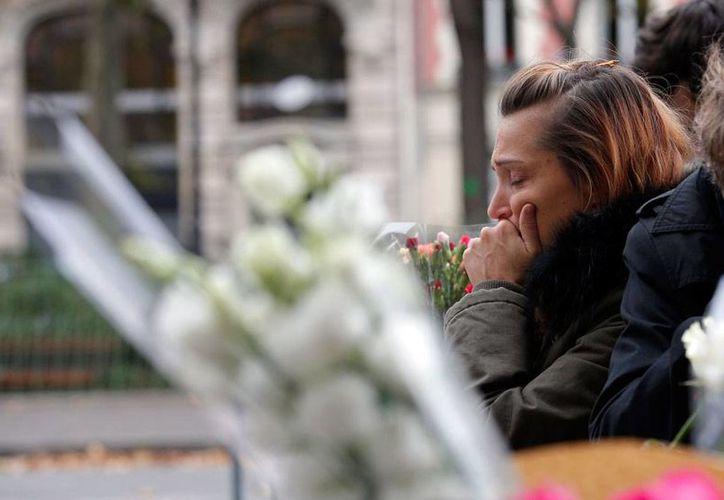 Una mujer deposita una ofrenda en las afueras de la sala de conciertos Bataclan, en París, Francia, donde un grupo de terroristas atacó a los asistentes a un concierto. (AP)