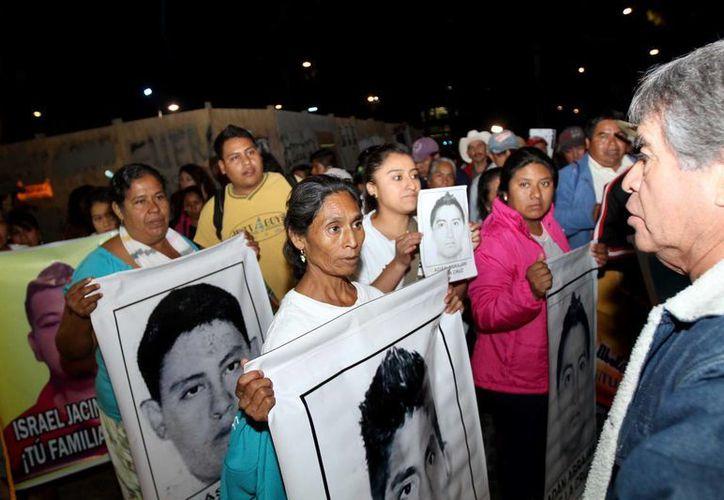 Los padres de los normalistas siguen pidiendo la aparición con vida de sus hijos. Imagen de contexto de una manifestación por los estudiantes de Ayotzinapa. (Notimex)