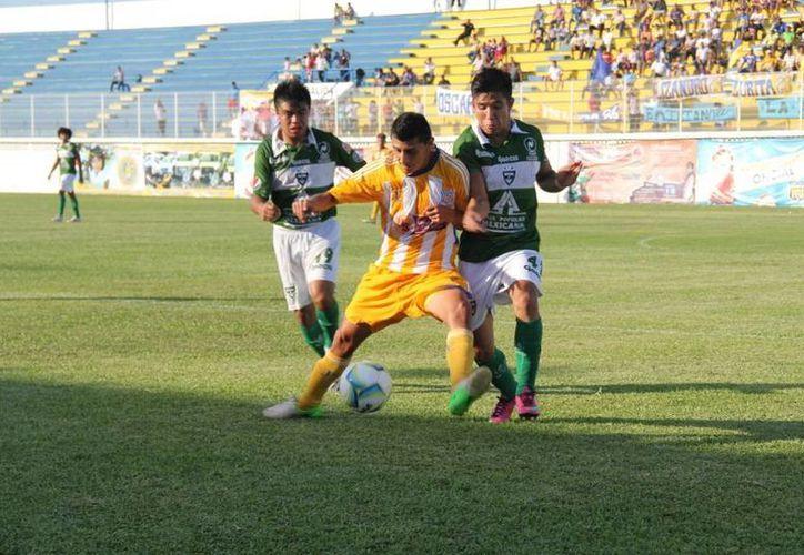 El delantero pionero Lizandro Echeverría es marcado por dos zagueros cañeros. (Ángel Mazariego/SIPSE)