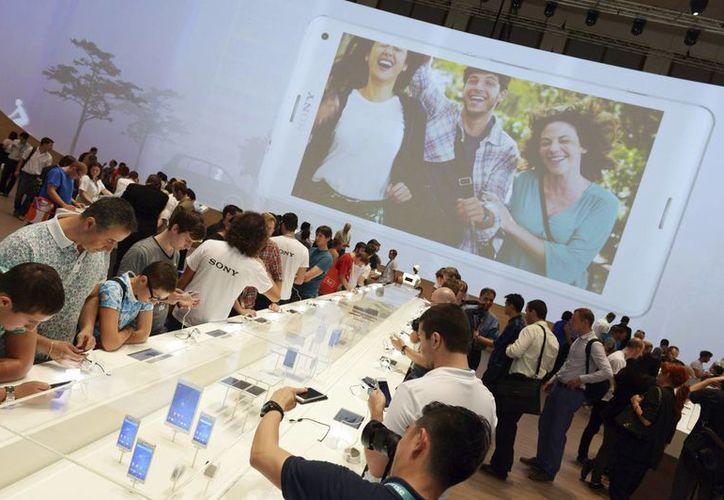 Numerosas personas observan teléfonos que se muestran en el estand de Sony durante la Feria Internacional de Electrónica de Consumo (IFA) que se celebra en Berlín, Alemania. (EFE)