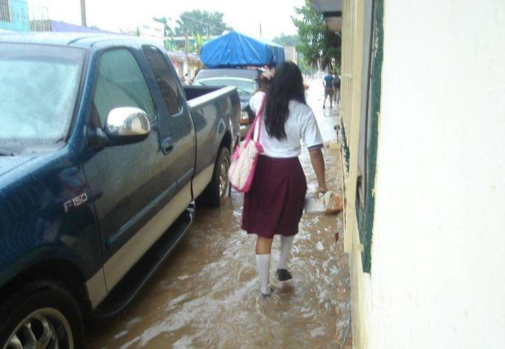Morelenses se vieron obligados a continuar sus actividades con las calles inundadas. (Carlos Yabur/SIPSE)