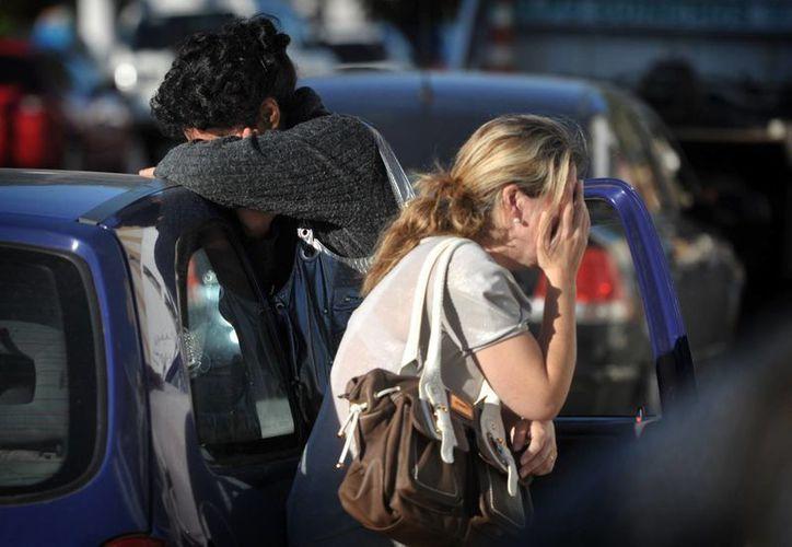 Una mujer llora al enterarse que su familiar estaba entre las víctimas de la discoteca Kiss. (AP)