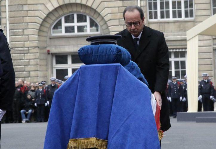 El presidente Francoise Hollande ante el féretro de uno de los agentes a quienes impuso la Legión de Honor, este martes 13 de enero de 2015, en París, Francia. (Foto AP)